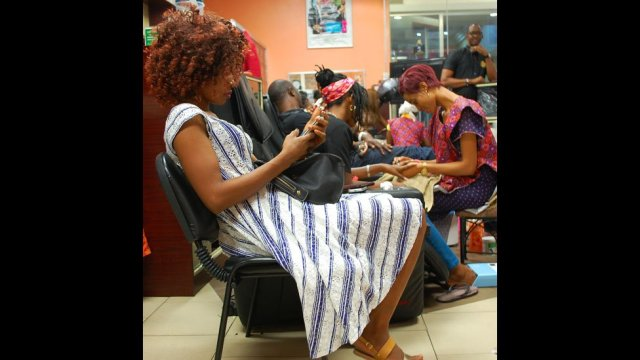 A customer reading her phone at Bruno's Place hair salon in Ikeja Mall in Lagos, Nigeria