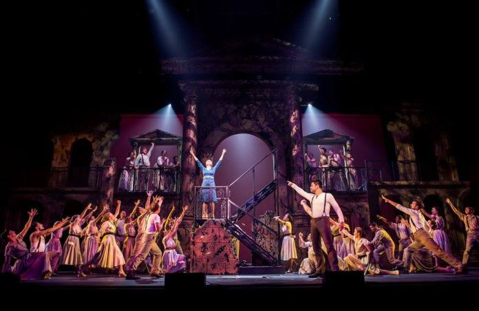 Photo of cast on-stage during a performance of Evita