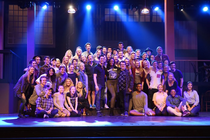 Quarrels, Gibbs and Strand stand with a class of students on stage in the Massey Performing Arts Center
