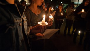 Students hold candles at a previous MLK Day candlelight vigil on campus