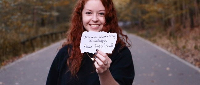 Burnett holding a sign with the name of her New Zealand university