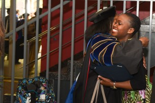 A student hugs a faculty member following awards day