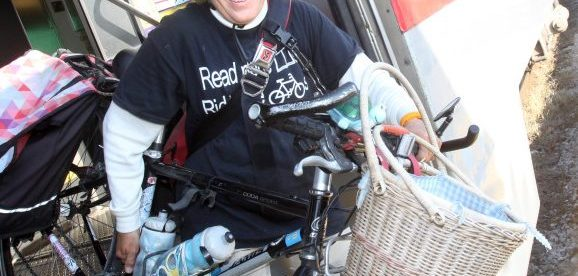 Sally Robertson smiling on bike, wearing library tshirt