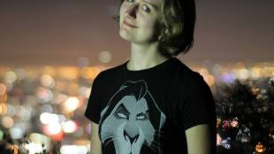 Bethany Brinton smiling in front of a cityscape at night