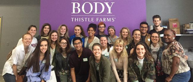 Students standing in front of Thistle farms banner, which reads,