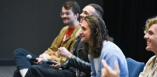 The members of COIN seated in a row, smiling at the audience