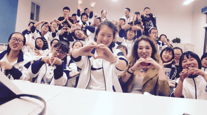 Students holding out their hands in the shape of hearts toward the camera