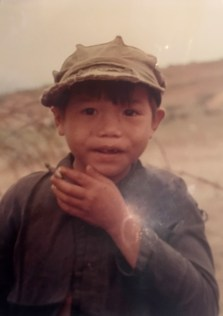 Young Vietnamese boy, frowning at the camera