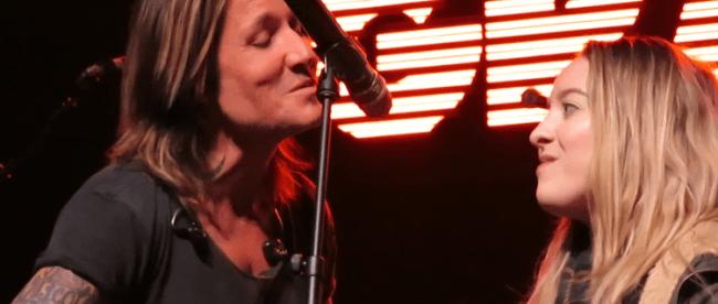 Ashley Sorenson sings into microphone with Keith Urban