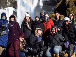 students and faculty, bundled in winter clothes, posing in front of a waterfall