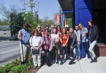 Students stand beside the Dogwood trees by The Belmont Store to celebrate Arbor Day.
