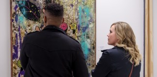 two people looking at a painting