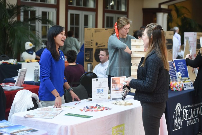 Student talks with community vendor at Health and Well-being fair