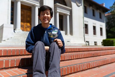 Justin Yim sits on steps holding a small robot