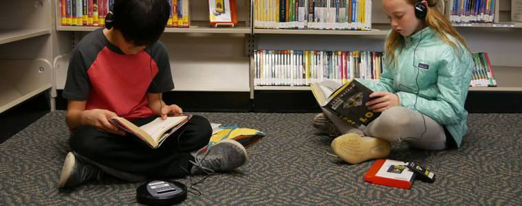 Zander Chao and Hannah Smith listen to books while they read.