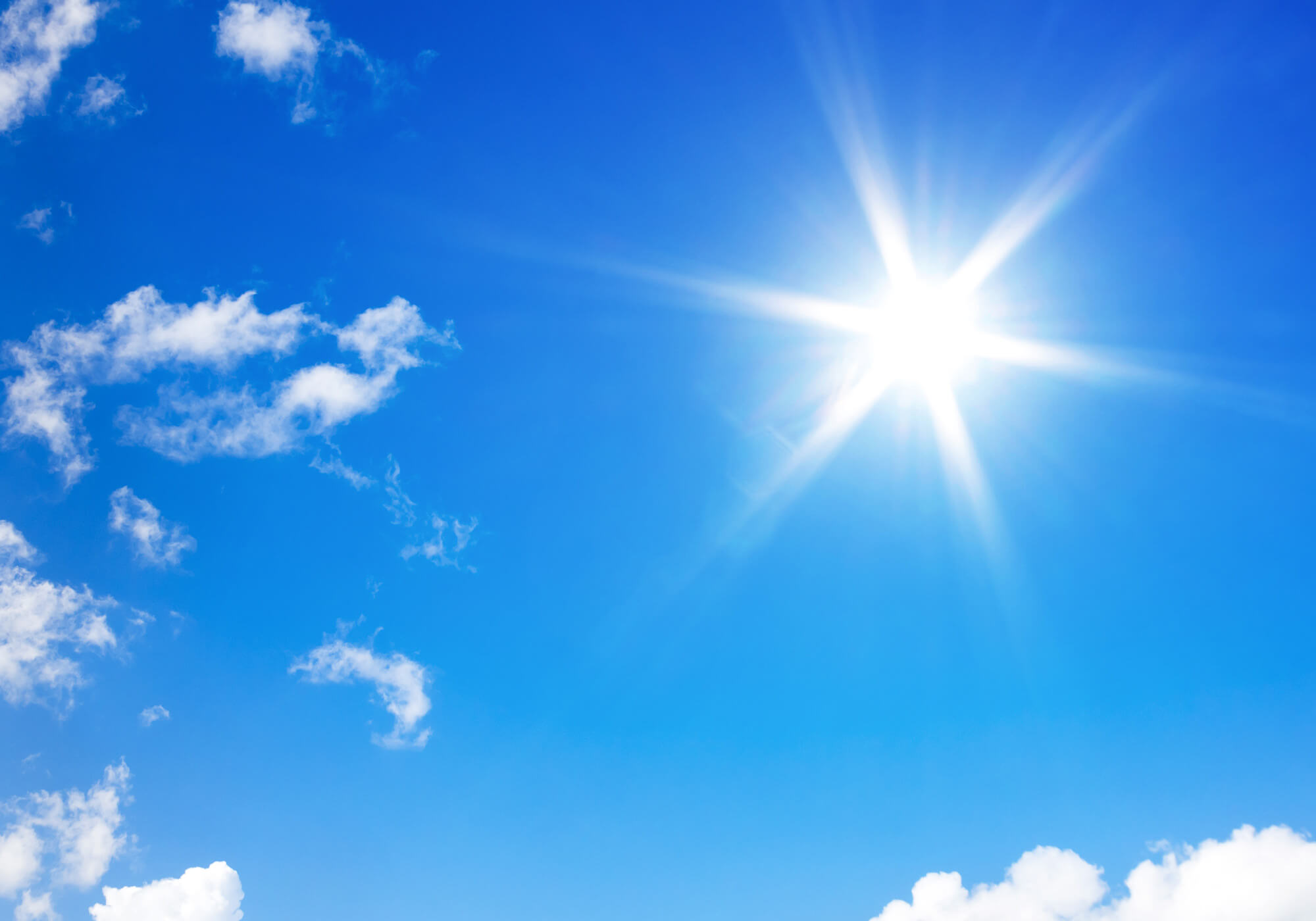 bright sun in the blue sky with wispy clouds
