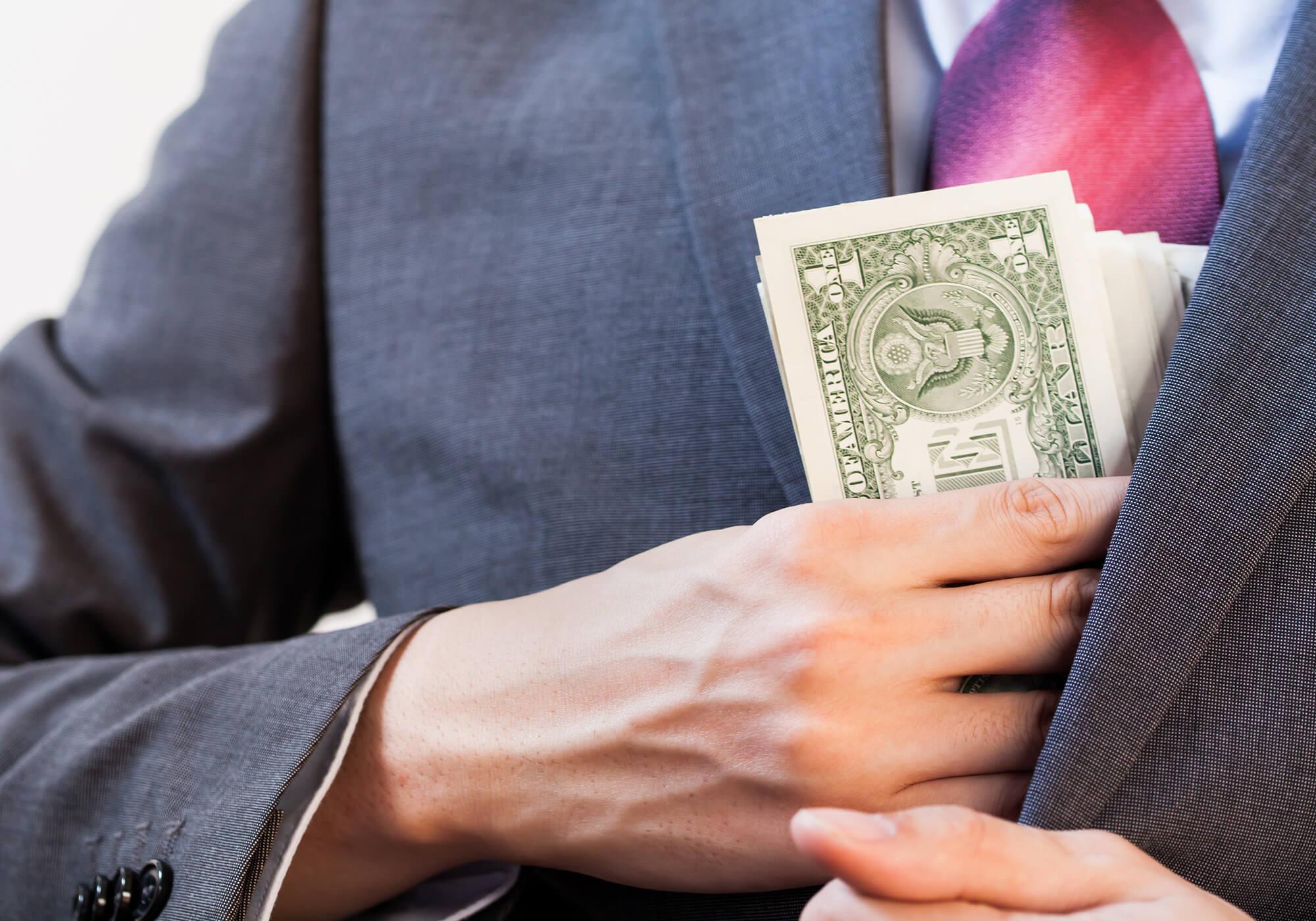 person in suit hiding dollar bills inside jacket