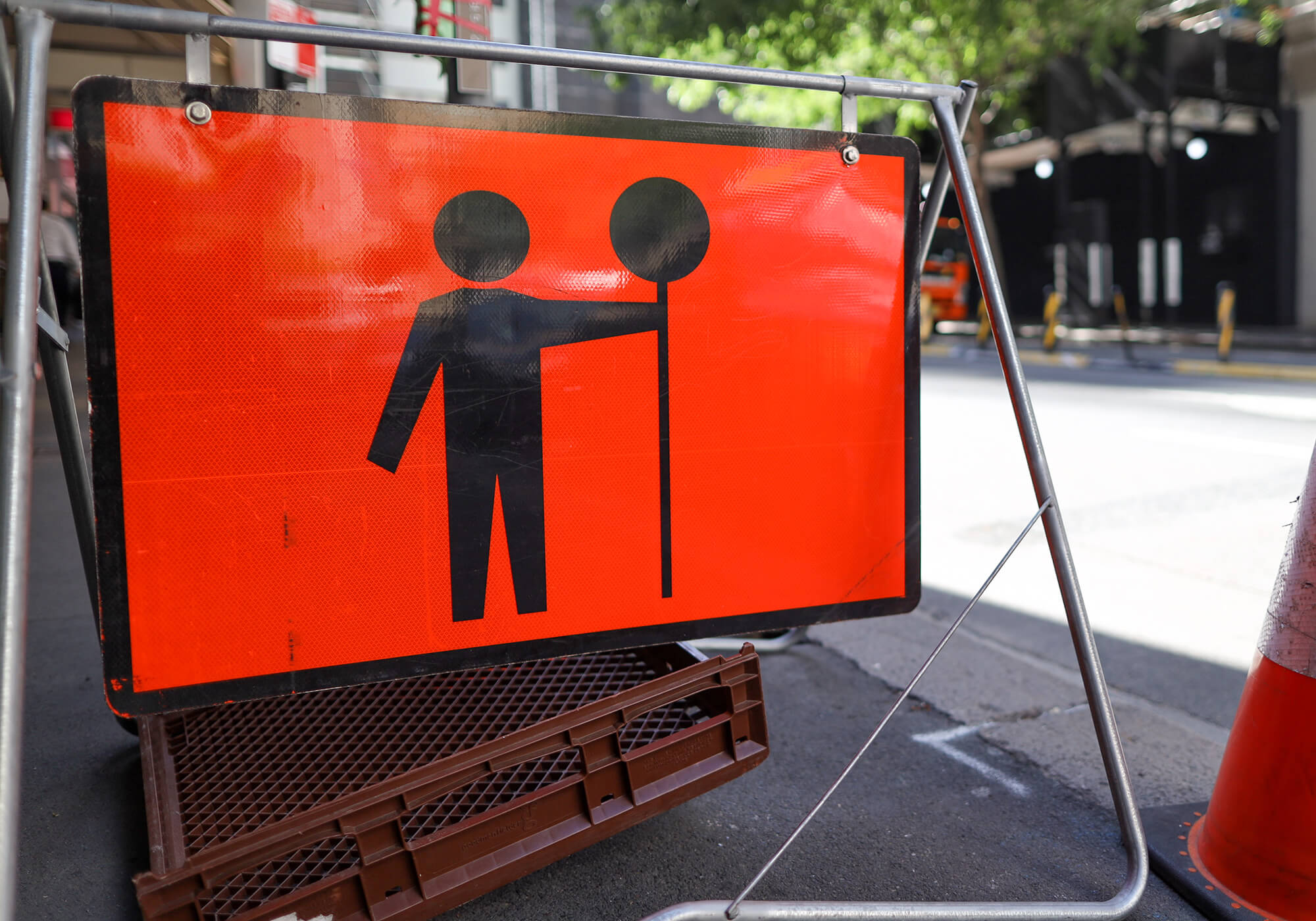 orange construction sign with silhouette of flagger