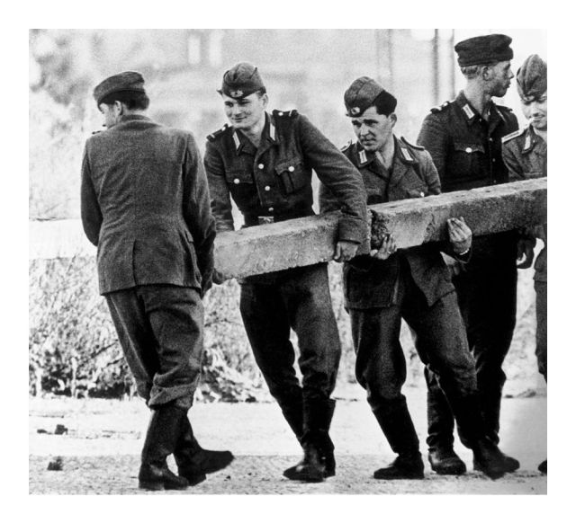 East German soldiers build the Berlin Wall and close access to West Berlin, 1961.