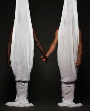 nude men holding hands, bodies obscured by hanging sheets