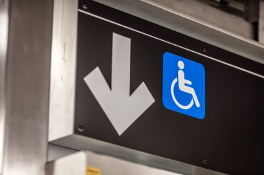 MTA elevator sign with arrow pointing down with wheelchair next to it
