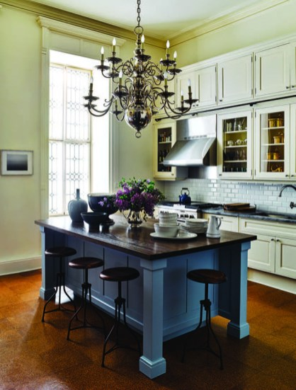 In the high-ceilinged kitchen, they added the substantial island and the two-tier, Flemish style chandelier (in a nickel finish that goes with the appliances and fixtures).