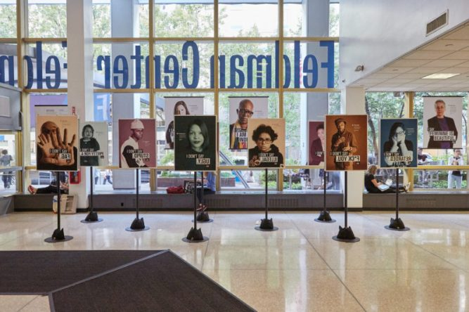 posters from the Impactful Language exhibition hanging the the lobby of FIT's Feldman Center