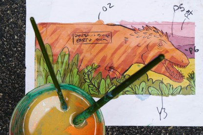 cup of water with paintbrushes shot from above over sketch of dinosaur