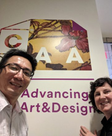 CJ Yeh and Austin Thomas post in front of CAA poster