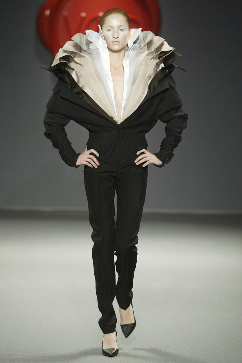 Model in black suit with layers of white colored shiirts