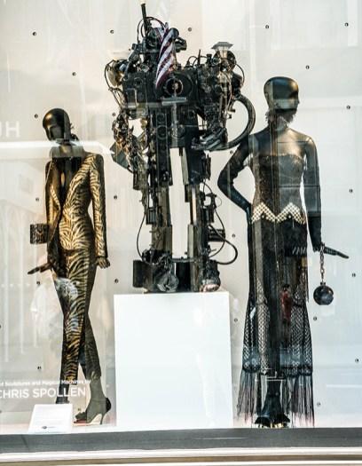 mannequin in metallic suitmannequin in sequin dresses with metal robot sculptures