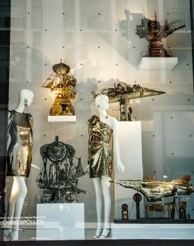 two mannequins in metallic dresses with metal robot sculptures
