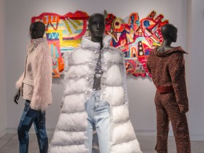 three mannequins with clothing and fabric art in the background