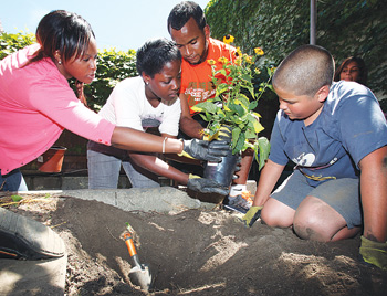 Middle school students from the Liberty Partnerships Program (LPP) applied what they learned about flora to plant a garden behind the LPP office. From left, Diane Ode, GSS '11, helps LLP students Taiah Smith and Alejandro Sanjaio (right) with a garden project. Photo by Bruce Gilbert