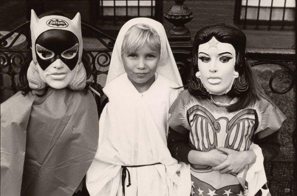 Three kids dressed for Halloween as Batgirl, St. Ann, and Wonder Woman