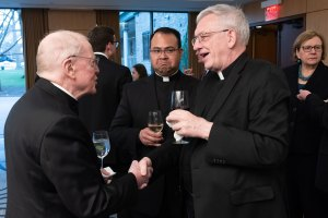 Priests talk to each other at a reception.