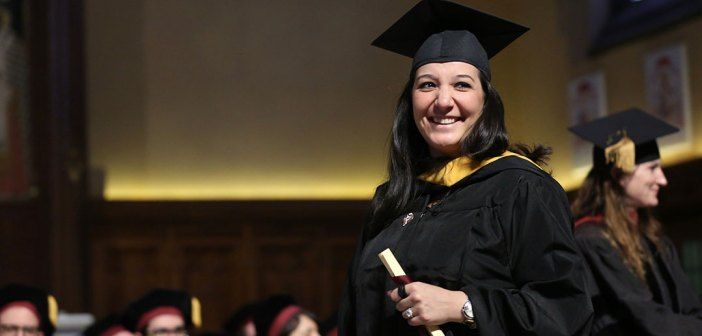 A woman holds a scroll while wearing a black academic robe.