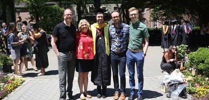A family poses for a picture with a graduate