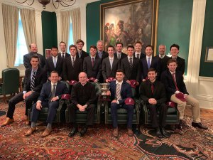 The hockey team seated with Father McShane