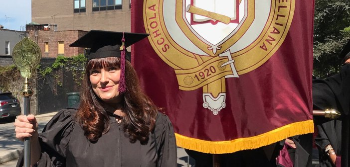 Woman in black academic robe poses with red and yellow banner