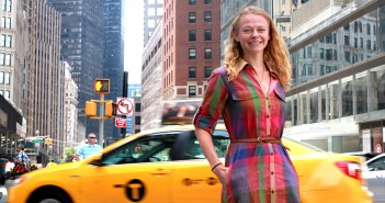A woman poses in front of a taxi in NYC