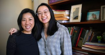 Two women stand and smile in front of a bookshelf.