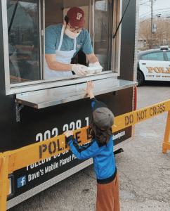 A young man wearing a maroon Fordham cap and standing in a food truck gives a tray of food to a little boy.