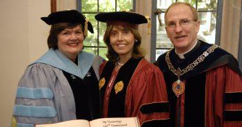 A woman wearing a blue graduation robe, a woman wearing a maroon graduation robe, and a man wearing a maroon graduation robe smile at the camera together.