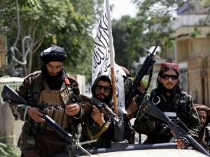 Taliban fighters display their flag on patrol in Kabul, Afghanistan,