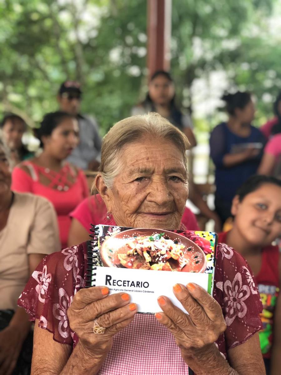 Consuelo, one of Lazaro Cardenas's female elders, holds the cookbook. With the cookbook, women hope to pass on their knowledge about using traditional plants to the next generation. Kevin Ferrara, DAI