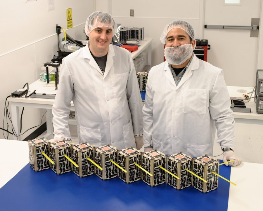 Two scientists with a small swarm of CubeSats capable of collecting and transferring scientific data. NASA Ames Research Center