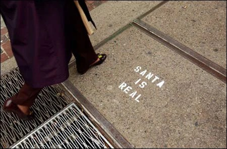 Photo of 'Santa is real' graffiti on sidewalk