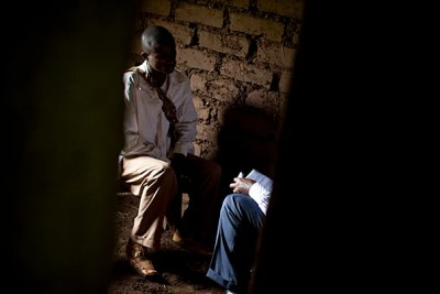 Two men sit close, knees almost touching, in a mud-walled hut in the Congolese village of Katokota.
