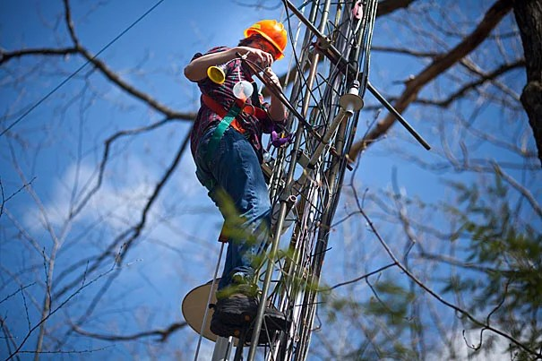 Harvard University research technician Josh McLaren works on a tower collecting environmental data at the Harvard Forest in Petersham, Mass.